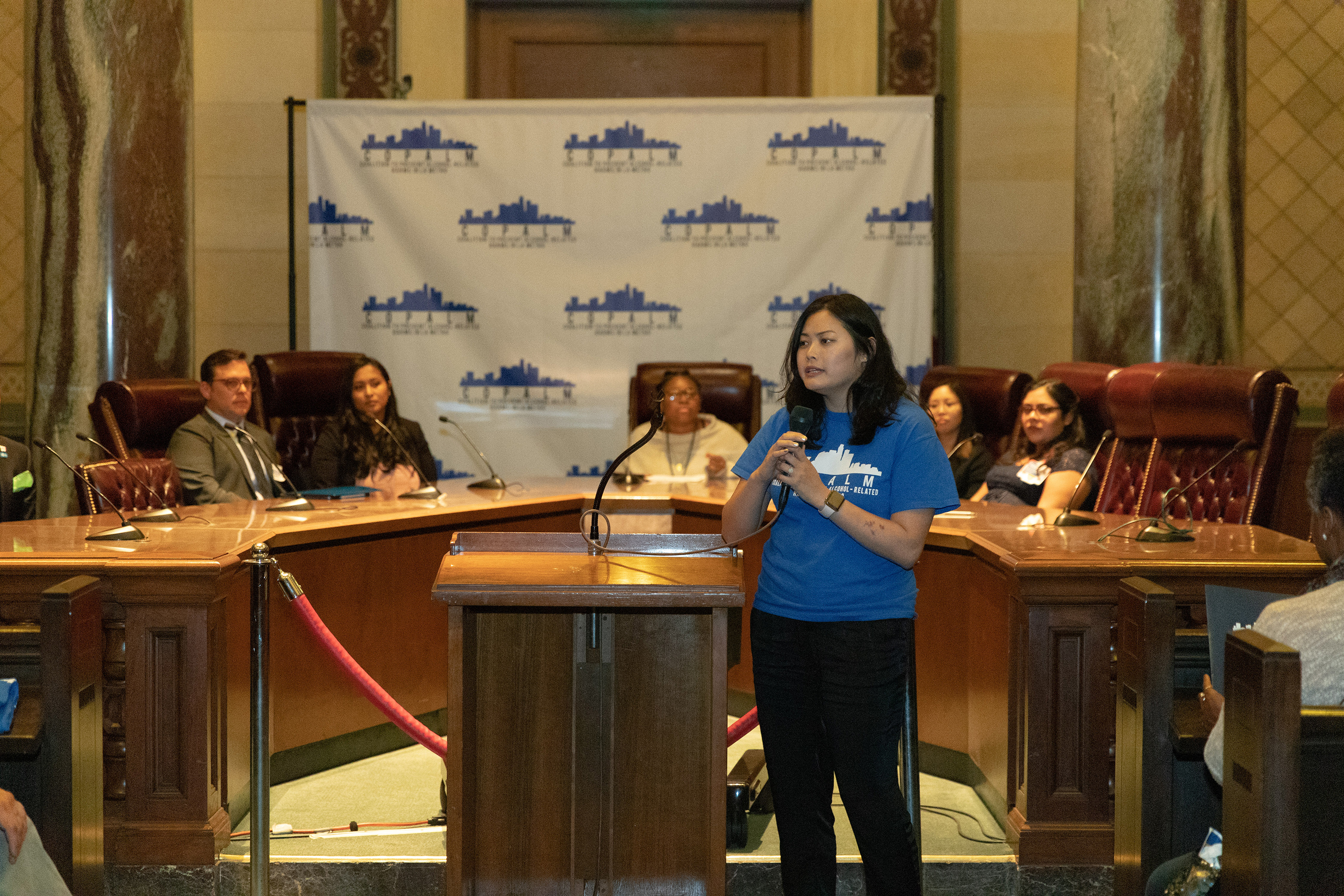 Member of CoPALM speaking into microphone at Los Angeles City Hall Chambers